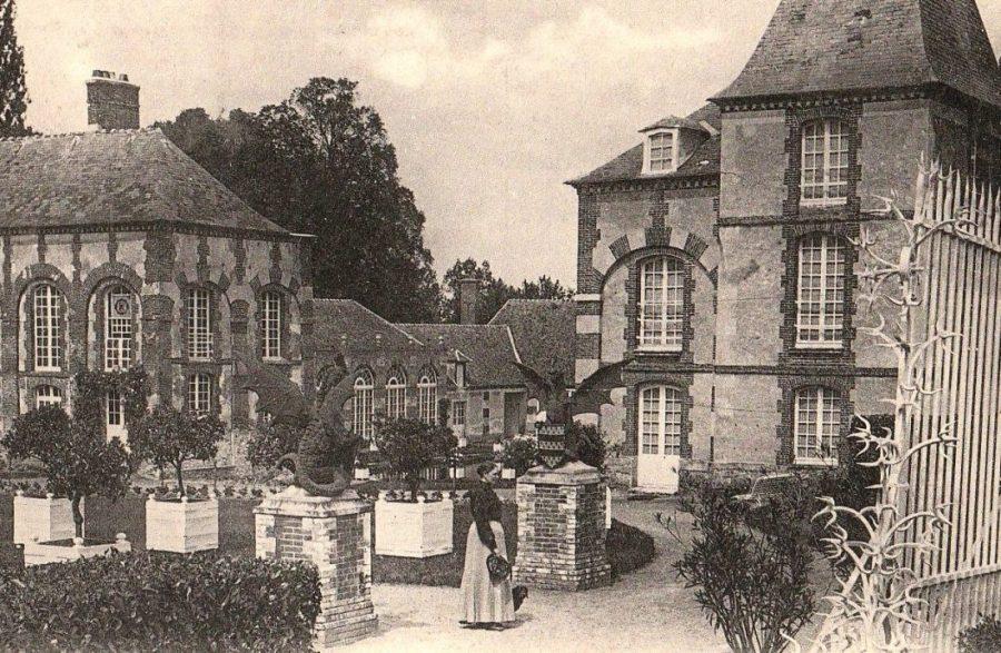L'entrée du château.  On distingue à droite l'extrémité de la grille récupérée au château royal de Saint-Hubert, aujourd'hui détruit. Il était situé à quelques kilomètres, au lieu-dit des Bréviaires, au bord des étangs de Hollande. Au milieu, les majestueux cockatrix, symboles de la famille Nugent depuis plusieurs siècles, furent fondus et mis en place par François, comte de Nugent et préfet. Entre les deux, l'ouverture de la cour d'honneur vers les communs dont on aperçoit l'orangerie, installée par le même François de Nugent. A gauche en retrait, on reconnait au bout de l'aile Est du château l'entrée de la chapelle entourée de lierre, laquelle fut emménagée encore par François de Nugent. Cette chapelle tenait sur deux niveaux : la tribune occupait le niveau supérieur, seulement accessible depuis l'intérieur du premier étage.